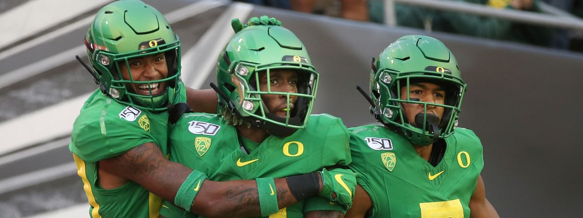 Oregon's Bryan Addison, left, Daewood Davis and Johnny Johnson III celebrate a fourth-quarter interception that Davis ran back for a touchdown against Nevada in an NCAA college football game Saturday, Sept. 7, 2019, in Eugene, Oregon.