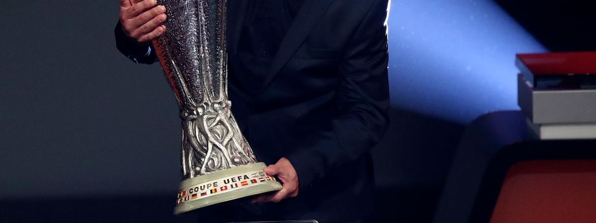 Former Poland midfielder Andrzej Buncol places the Europa League trophy during the UEFA group stage draw at the Grimaldi Forum, in Monaco, Friday, Aug. 30, 2019.