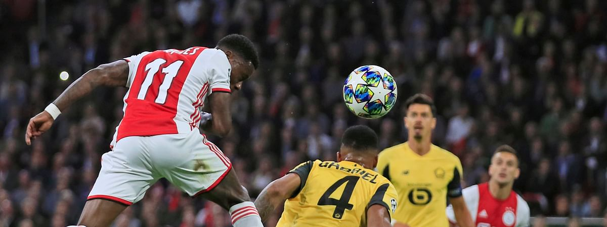 Ajax's Quincy Promes, left, scores his side's first goal with a header during the group H Champions League soccer match between Ajax and LOSC Lille at Johan Cruyff ArenA in Amsterdam, Netherlands, Tuesday, Sept. 17, 2019. (AP Photo/Peter Dejong)