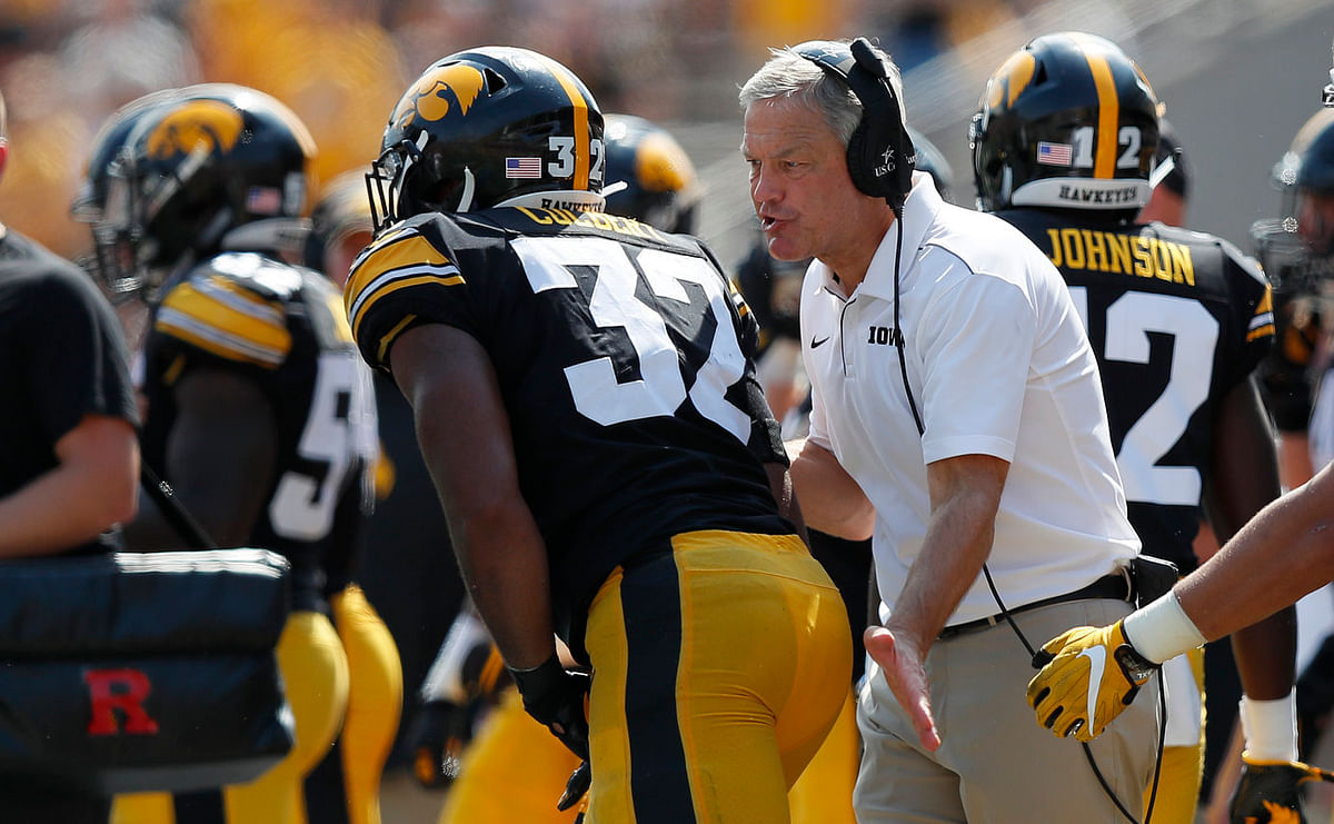 Iowa head coach Kirk Ferentz (right) talks with linebacker Djimon Colbert after a play against Rutgers on Sept. 7 (Matthew Putney)
