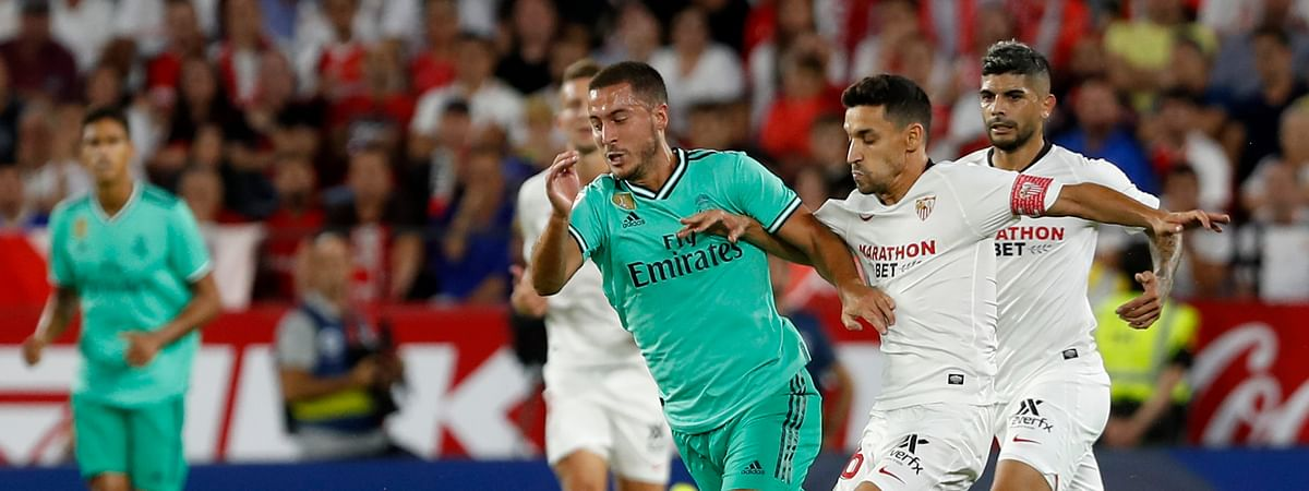Real Madrid's Eden Hazard, center, is challenged by Sevilla's Daniel Carrico during the Spanish La Liga soccer match between Sevilla and Real Madrid at the Ramon Sanchez Pizjuan stadium in Seville, Spain, Sunday, Sept. 22, 2019.