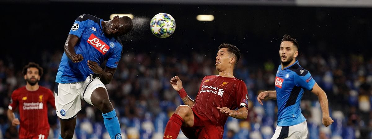 Napoli's Kalidou Koulibaly, left, heads the ball as Liverpool's Roberto Firmino tries to stop him during the Champions League Group E soccer match between Napoli and Liverpool, at the San Paolo stadium in Naples, Italy, Tuesday, Sept. 17, 2019.