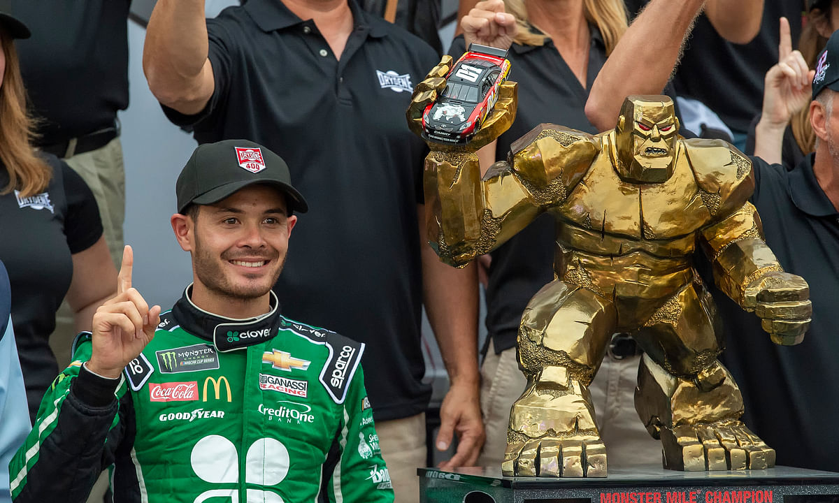Kyle Larson stands next to the trophy after winning the NASCAR Cup Series auto race Sunday, Oct. 6, 2019, at Dover International Speedway in Dover, Del. (AP Photo/Jason Minto)