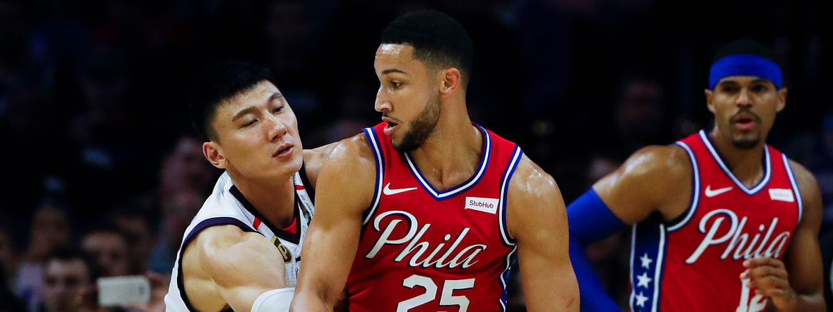Philadelphia 76ers' Ben Simmons (25) drives to the net as Guangzhou Loong-Lions' Yongpeng Zhang defends and Philadelphia 76ers' Tobias Harris, right, watches during the first half of an NBA exhibition basketball game Tuesday, Oct. 8, 2019, in Philadelphia.
