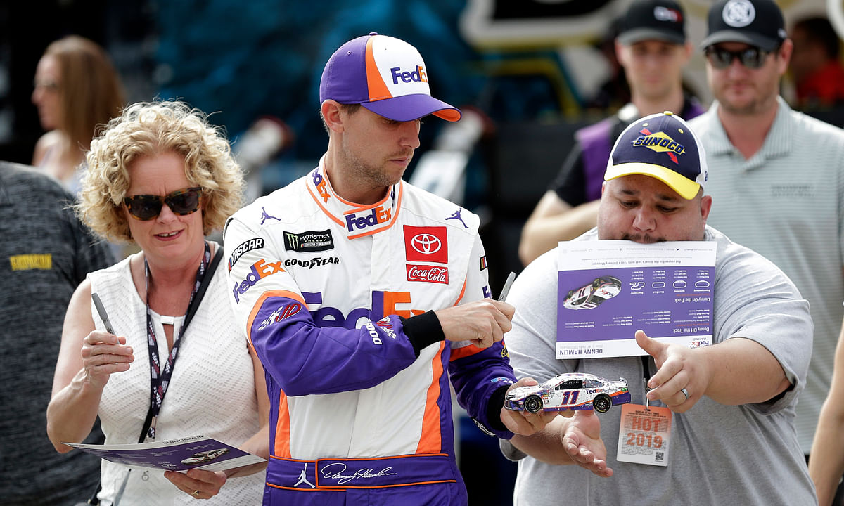 Denny Hamlin signs autographs during practice for Sunday's NASCAR Cup Series auto race at Charlotte Motor Speedway in Concord, N.C., Saturday, Sept. 28, 2019. (AP Photo/Gerry Broome)