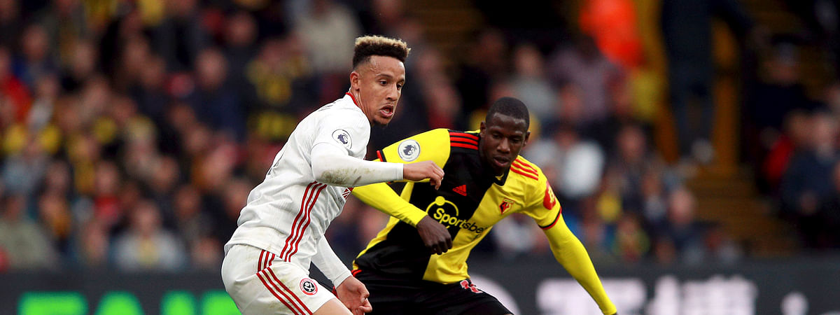 Sheffield United's Callum Robinson, left, and Watford's Abdoulaye Doucoure battle for the ball during the English Premier League soccer match at Vicarage Road, Watford, England, Saturday Oct. 5, 2019. (Ian Walton/PA via AP)