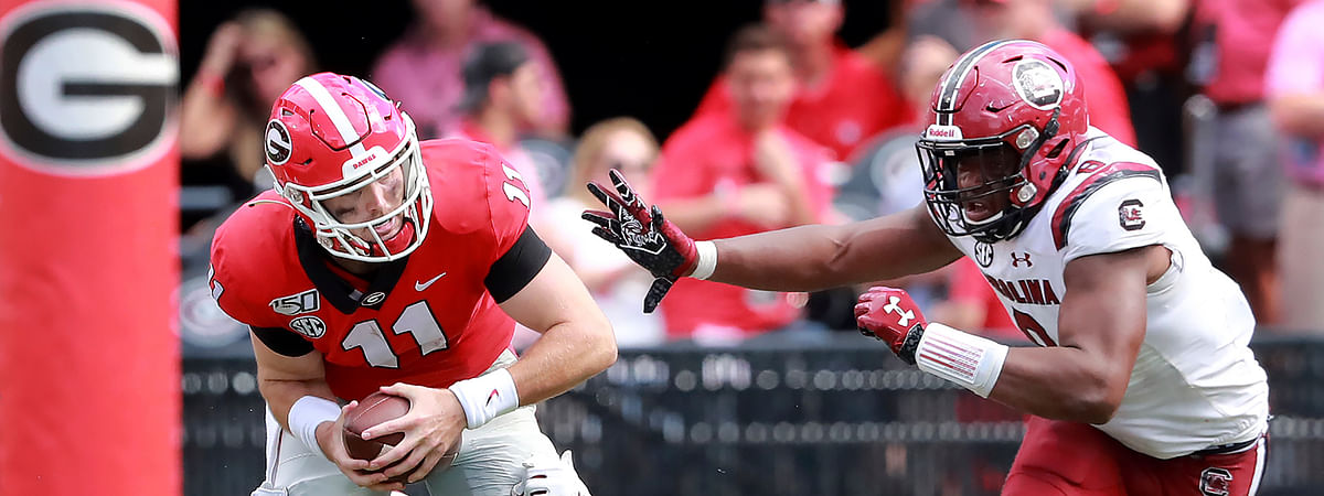 Georgia quarterback Jake Fromm is sacked by South Carolina defenders Kobe Smith, left, and D.J. Wonnum during the third quarter of an NCAA college football game, Saturday, Oct., 12, 2019, in Athens, Ga. (Curtis Compton/Atlanta Journal-Constitution via AP)
