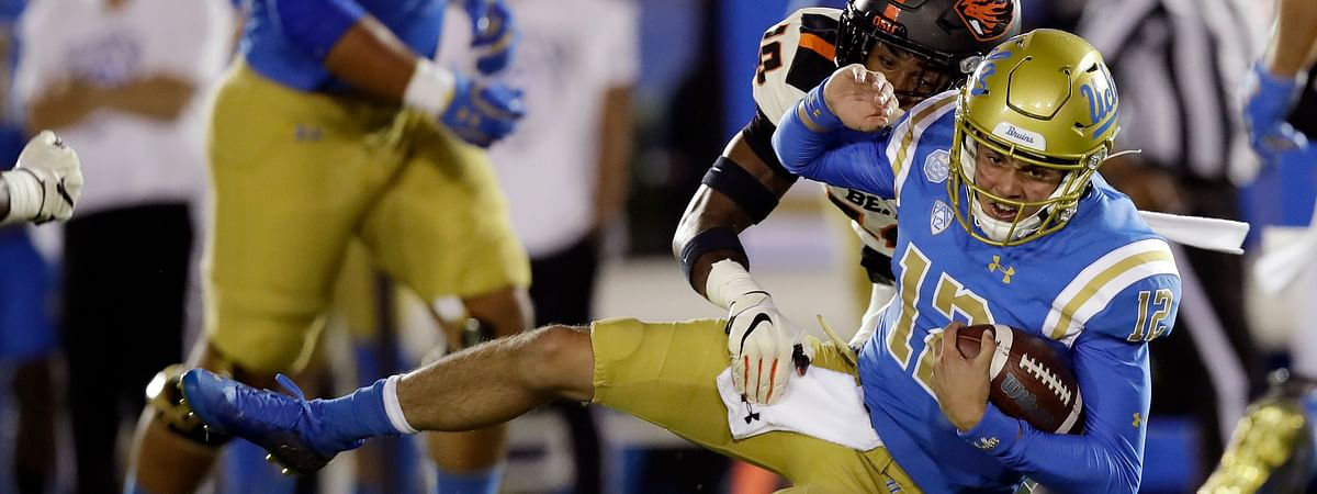 UCLA quarterback Austin Burton (12) is tackled y Oregon State defensive back Omar Hicks-Onu, top, during the first half of an NCAA college football game Saturday, Oct. 5, 2019, in Pasadena, California.