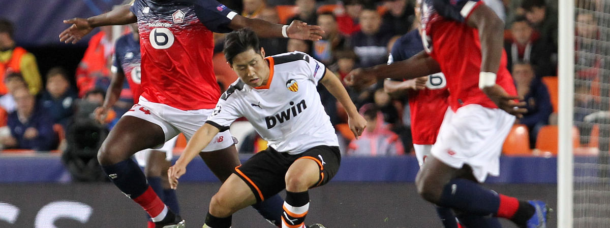 Valencia's Lee Kang-in, center, vies for the ball with Lille's Boubakary Soumare, left, during the Champions League group H soccer match between Valencia and Lille at the Mestalla stadium in Valencia, Spain, Tuesday, Nov. 5, 2019.