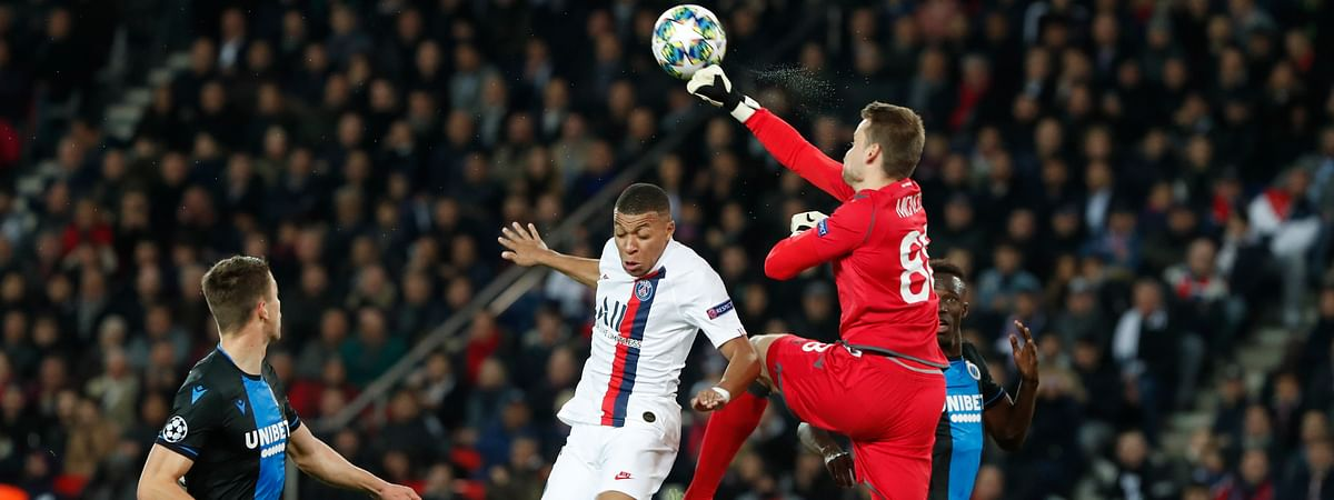 PSG's Kylian Mbappe, center, jumps for the ball as Brugge goalkeeper Simon Mignolet block the ball during a Champions League group A soccer match between Paris Saint Germain and Club Brugge, at the Parc des Princes stadium, in Paris, Wednesday, Nov. 6, 2019.