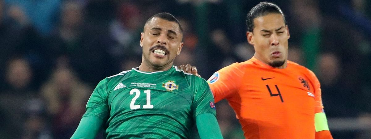 Northern Ireland's Josh Magennis jumps for the ball with Netherlands' Virgil Van Dijk, right, during the Euro 2020 group C qualifying soccer match between Northern Ireland and the Netherlands at Windsor Park, Belfast, Northern Ireland, Saturday, Nov. 16, 2019.