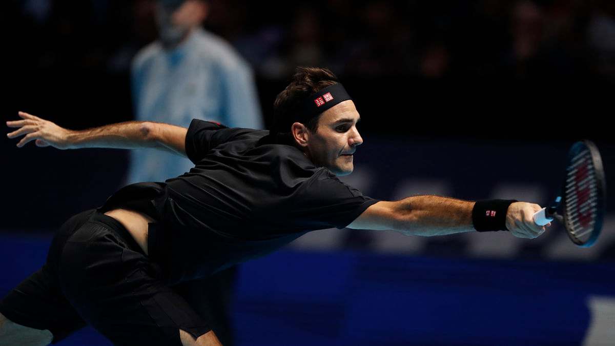 Switzerland's Roger Federer plays a return to Italy's Matteo Berrettini during their ATP World Tour Finals singles tennis match at the O2 Arena in London, Tuesday, Nov. 12, 2019.