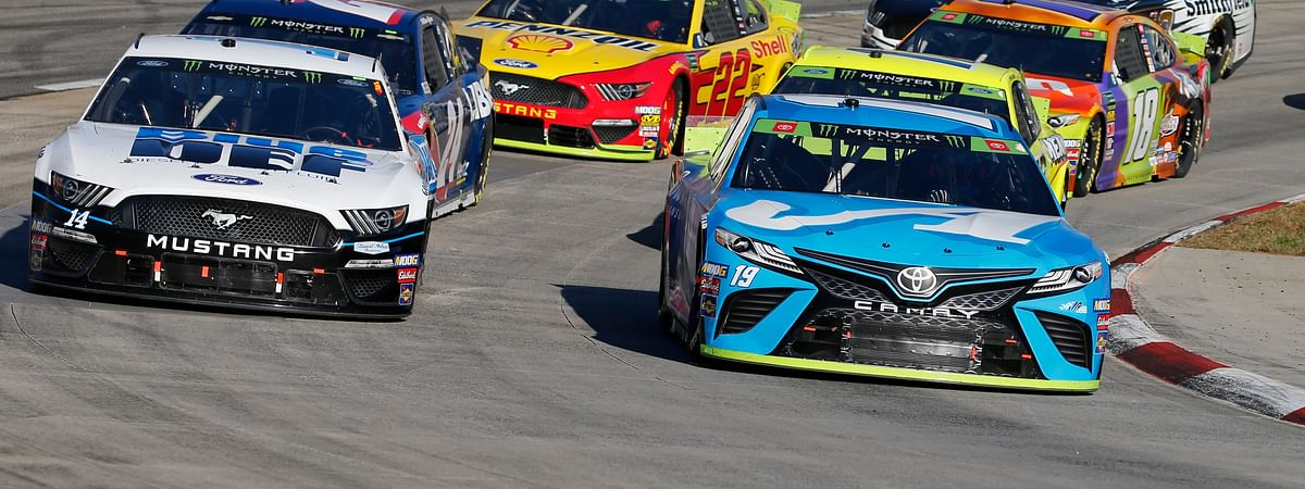 Martin Truex Jr. (19) and Clint Bowyer (14) lead the field in turn four during a restart of the NASCAR Cup Series race at Martinsville Speedway in Martinsville, Va., Sunday, Oct. 27, 2019.