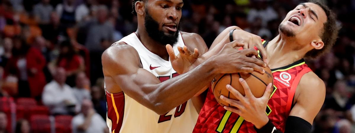 Miami Heat forward Justise Winslow (20) fights for the ball with Atlanta Hawks guard Trae Young (11) during the first half of an NBA basketball game Tuesday, Oct. 29, 2019, in Miami. (AP Photo/