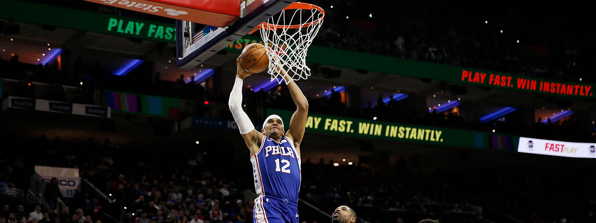 Philadelphia 76ers' Tobias Harris (12) goes up for a dunk as Cleveland Cavaliers' Tristan Thompson (13) looks on during the first half of an NBA basketball game, Tuesday, Nov. 12, 2019, in Philadelphia. (AP Photo/Matt Slocum)