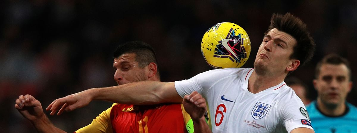 England's Harry Maguire, right, and Montenegro's Fatos Beciraj fight for the ball during the Euro 2020 group A qualifying soccer match between England and Montenegro at Wembley stadium in London, Thursday, Nov. 14, 2019.