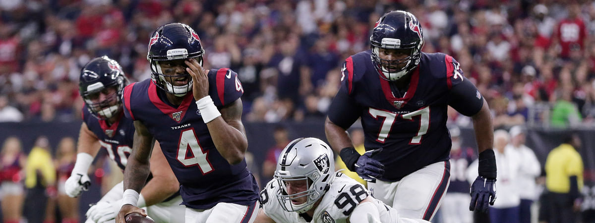 Houston Texans quarterback Deshaun Watson (4) holds his eye as he is pressured by Oakland Raiders defensive end Maxx Crosby (98) as he looks pass during the second half of an NFL football game Sunday, Oct. 27, 2019, in Houston. Watson completed the pass to tight end Darren Fells for a touchdown. (AP Photo/Michael Wyke)
