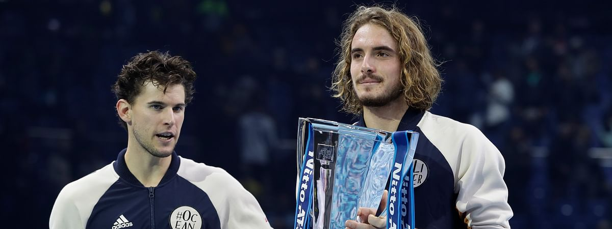 Stefanos Tsitsipas of Greece, right, and Austria's Dominic Thiem pose for the media with their trophies after the final of the ATP World Finals tennis match in which Tsitsipas defeated Thiem at the O2 arena in London, Sunday, Nov. 17, 2019.