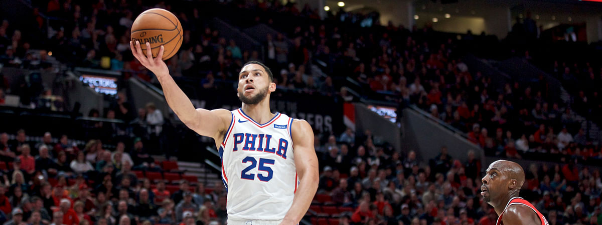 Philadelphia 76ers guard Ben Simmons, center, shoots between Portland Trail Blazers guard Damian Lillard, left, and forward Anthony Tolliver, right, during the first half of an NBA basketball game in Portland, Ore., Saturday, Nov. 2, 2019.