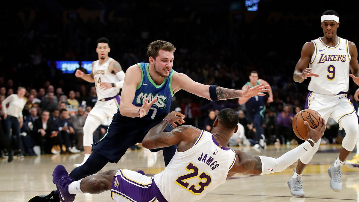 Los Angeles Lakers' LeBron James (23) recovers a loose ball under Dallas Mavericks' Luka Doncic (77) during the first half of an NBA basketball game Sunday, Dec. 1, 2019, in Los Angeles.