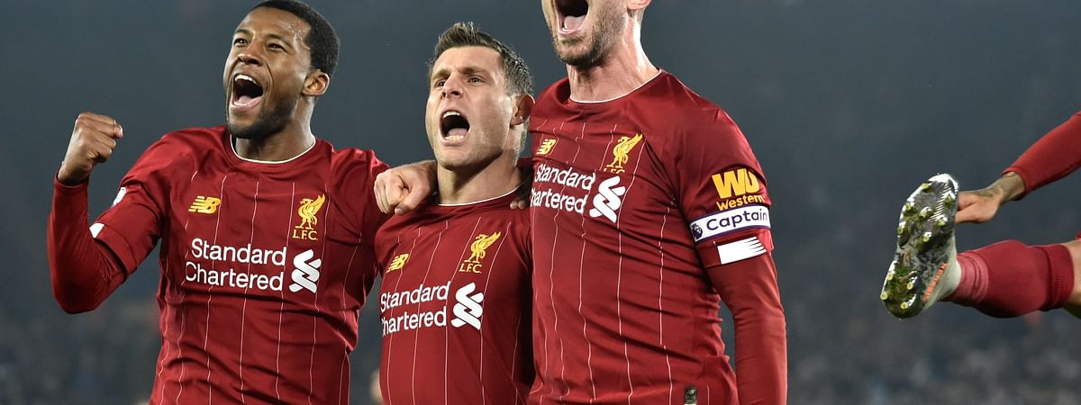 Liverpool's James Milner, second left, celebrates with his teammate Liverpool's Georginio Wijnaldum, left, and Liverpool's Jordan Henderson after scoring his side's second goal during the English Premier League soccer match between Leicester City and Liverpool at the King Power Stadium in Leicester, England, Thursday, Dec. 26, 2019.