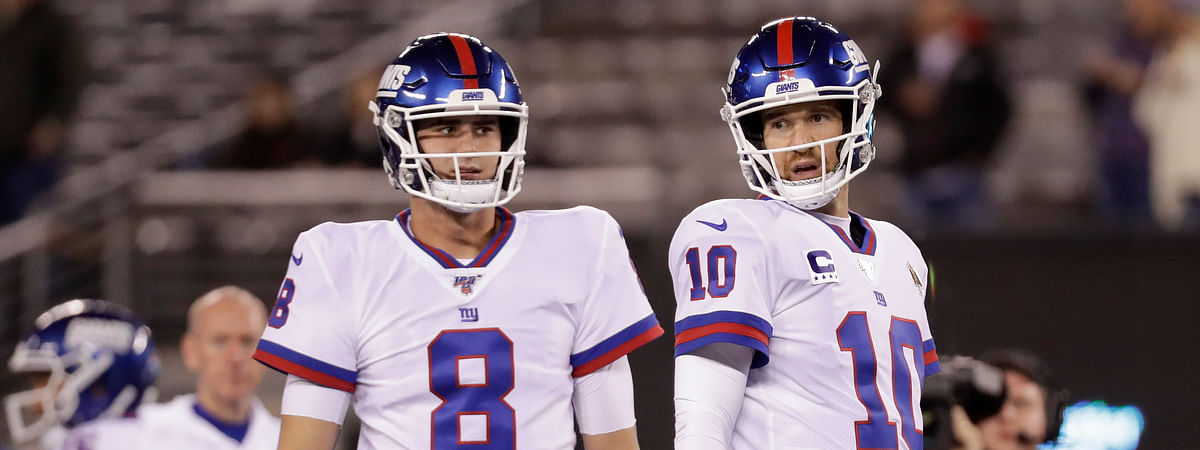 In this Nov. 4, 2019photo, New York Giants quarterback Daniel Jones (8) and quarterback Eli Manning (10) warm up before an NFL football game against the Dallas Cowboys, in East Rutherford, N.J.