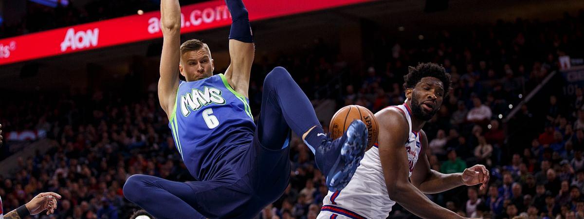 Dallas Mavericks' Kristaps Porzingis (6) dunks against Philadelphia 76ers' Joel Embiid, right, during the first half of an NBA basketball game, Friday, Dec. 20, 2019, in Philadelphia.