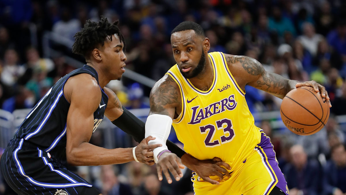 Los Angeles Lakers' LeBron James (23) drives around Orlando Magic's Wes Iwundu, left, during the first half of an NBA basketball game, Wednesday, Dec. 11, 2019, in Orlando, Fla. (AP Photo
