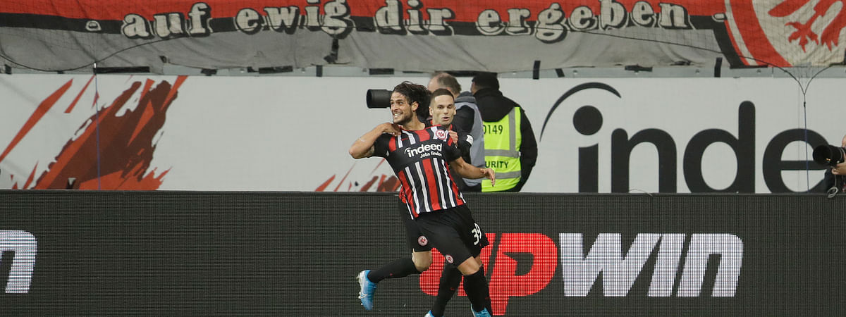 In this November 2019 file photo, Frankfurt's Goncalo Paciencia, left, celebrates after scoring his sides 5th goal of the game during the German Bundesliga soccer match between Eintracht Frankfurt and Bayern Munich in the Commerzbank Arena in Frankfurt, Germany.