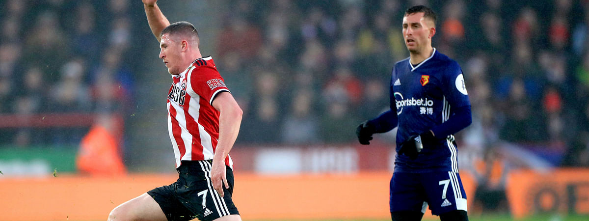 Sheffield United's John Lundstram, left, and Watford's Will Hughes battle for the ball during their English Premier League soccer match at Bramall Lane, Sheffield, England, Thursday, Dec. 26, 2019.