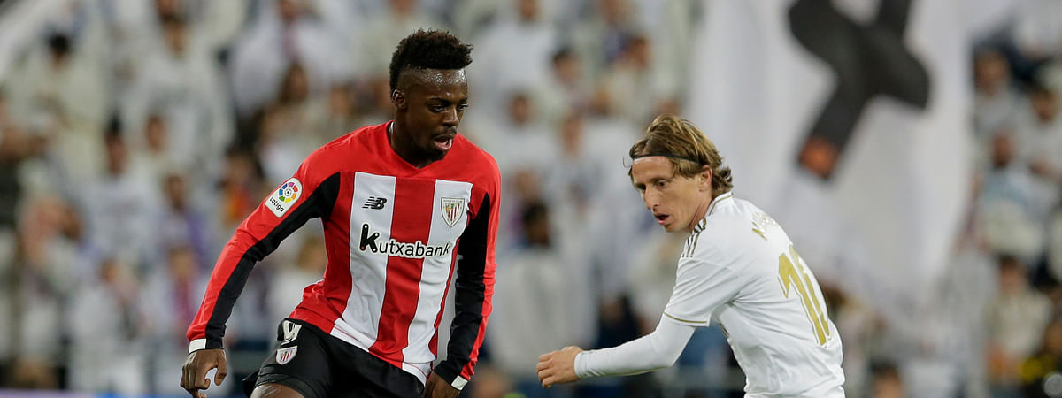 Athletic Bilbao's Inaki Williams, left, and Real Madrid's Luka Modric fight for the ball during a Spanish La Liga soccer match between Real Madrid and Athletic Bilbao at the Santiago Bernabeu stadium in Madrid, Spain, Sunday Dec. 22, 2019.