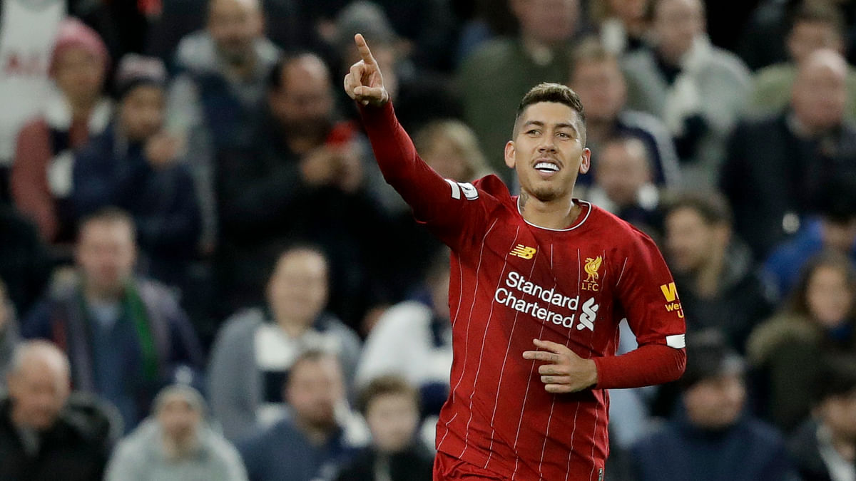 Liverpool's Roberto Firmino celebrates after scoring the opening goal during the English Premier League soccer match between Tottenham Hotspur and Liverpool at the Tottenham Hotspur Stadium in London, England, Saturday, Jan. 11, 2020.