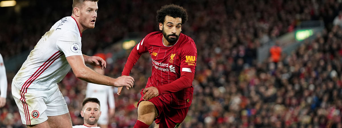 Sheffield United's Jack O'Connell, left, and Liverpool's Mohamed Salah run for the ball during the English Premier League soccer match between Liverpool and Sheffield United at Anfield Stadium, Liverpool, England, Thursday, Jan. 2, 2020.