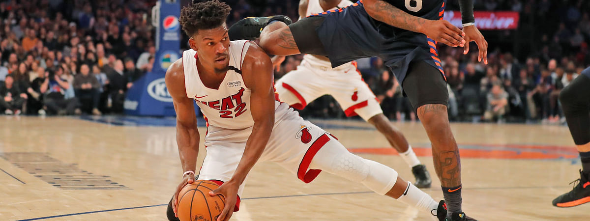 New York Knicks' Elfrid Payton, right, jumps over Miami Heat's Jimmy Butler as they scramble for a loose ball during the first half of the NBA basketball game, Sunday, Jan. 12, 2020, in New York.