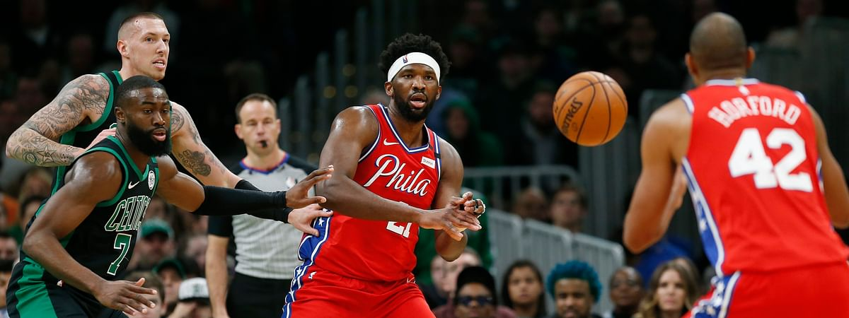 Philadelphia 76ers' Joel Embiid (21) passes to Al Horford (42) as Boston Celtics' Jaylen Brown (7) and Daniel Theis, back left, defend during the first half of an NBA basketball game in Boston, Saturday, Feb. 1, 2020.