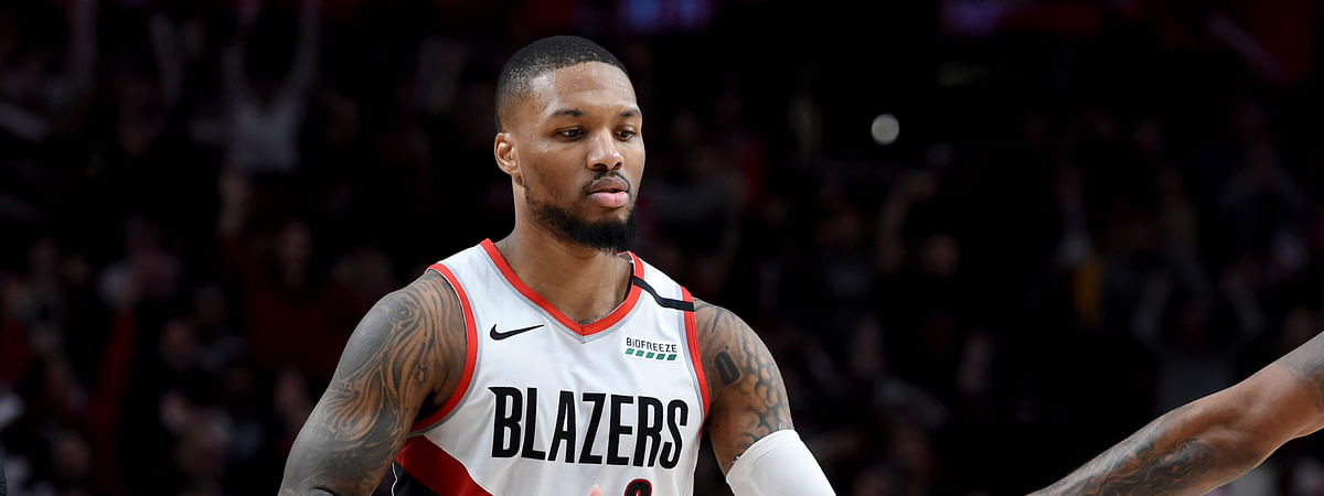 Portland Trail Blazers guard Damian Lillard is greeted by a teammate after scoring during the second half of an NBA basketball game against the Utah Jazz in Portland, Ore., Saturday, Feb. 1, 2020. The Blazers won 124-107.