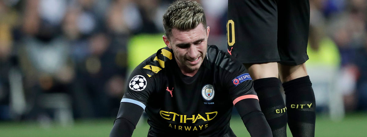 Manchester City's Aymeric Laporte sits injured on the pitch during the round of 16 first leg Champions League soccer match between Real Madrid and Manchester City at the Santiago Bernabeu stadium in Madrid, Spain, Wednesday, Feb. 26, 2020.