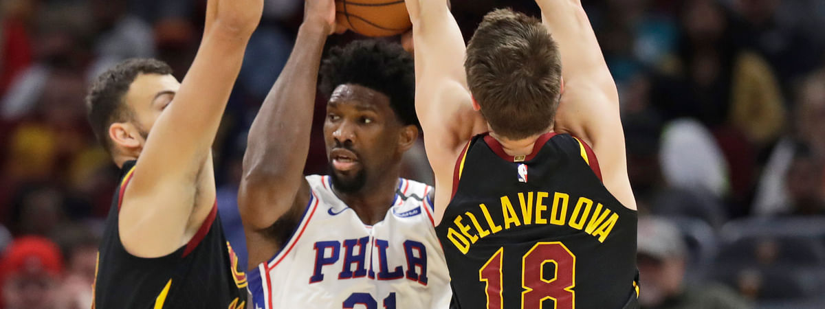 Philadelphia 76ers' Joel Embiid, center, squeezes between Cleveland Cavaliers' Ante Zizic, left and Matthew Dellavedova in the first half of an NBA basketball game, Wednesday, Feb. 26, 2020, in Cleveland.