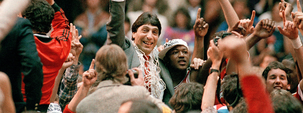 In this April 4, 1983, file photo, North Carolina State coach Jim Valvano, center with fist raised, celebrates after the team's win over Houston to win the NCAA men's basketball tournament championship in Albuquerque, N.M. This season's tournament, like all before them, would've been filled with dozens of legends in the making and diamonds in the rough _ with teams that overcame adversity to get this far and superfans who inspired the country every bit as much as their team.