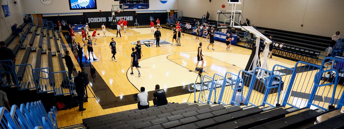 Yeshiva University players, foreground, warm up in a mostly empty Goldfarb Gymnasium at Johns Hopkins University before playing against Worcester Polytechnic Institute in a first-round game at the men's Division III NCAA college basketball tournament, Friday, March 6, 2020, in Baltimore, The university held the tournament without spectators after cases of COVID-19 were confirmed in Maryland. (AP Photo/Jessie Wardarski)