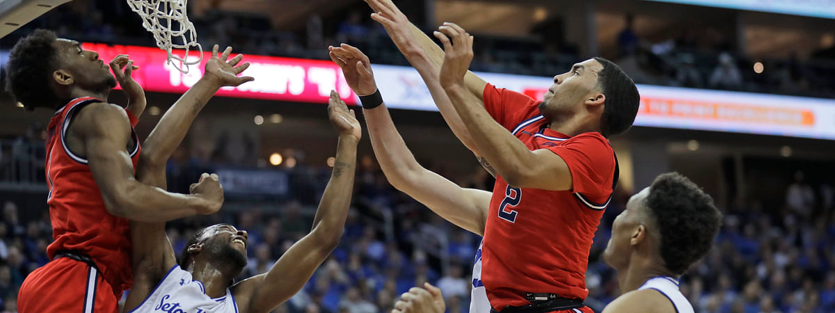 St. John's Julian Champagnie, top right, drives to the basket over Seton Hall defenders during the first half of an NCAA college basketball game in Newark, N.J., Sunday, Feb. 23, 2020.