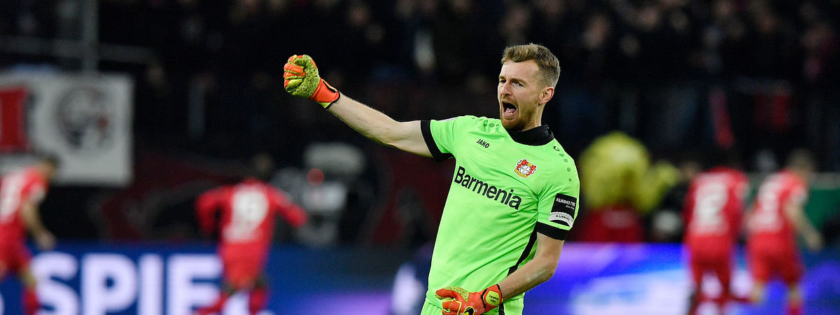 In this March 4, 2020 file photo, Leverkusen's goalkeeper Lukas Hradecky celebrates after his team scored the second goal during the German soccer cup, DFB Pokal, quarter-final match between Bayer Leverkusen and Union Berlin in Leverkusen, Germany.