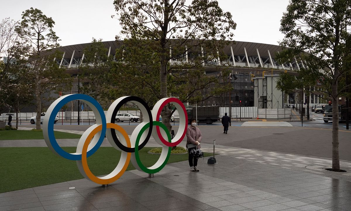 A woman pauses for photos next to the Olympic rings near the New National Stadium in Tokyo, Monday, March 23, 2020. The IOC will take up to four weeks to consider postponing the Tokyo Olympics amid mounting criticism of its handling of the coronavirus crisis that now includes a call for delay from the leader of track and field, the biggest sport at the games.