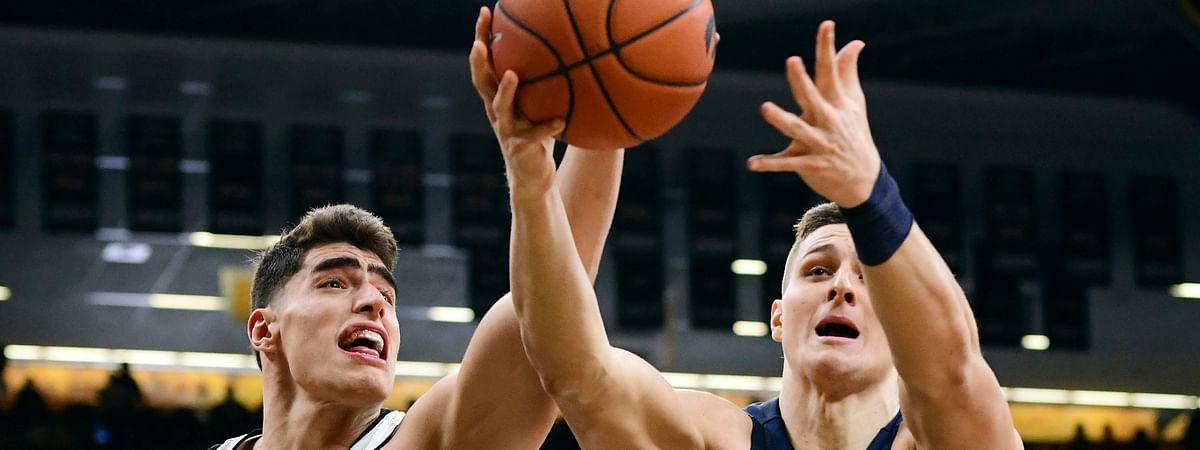 Iowa's Luka Garza (55) and Penn State's John Harrar reach for a rebound during the first half of an NCAA college basketball game, Saturday, Feb. 29, 2020, in Iowa City, Iowa. (AP Photo/Cliff Jette)