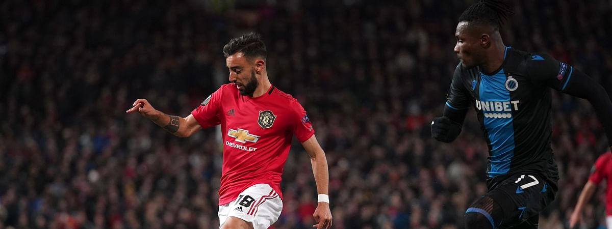 Manchester United's Bruno Fernandes, left, and Brugge's Simon Deli run for the ball during the round of 32 second leg Europa League soccer match between Manchester United and Brugge at Old Trafford in Manchester, England, Thursday, Feb. 27, 2020.