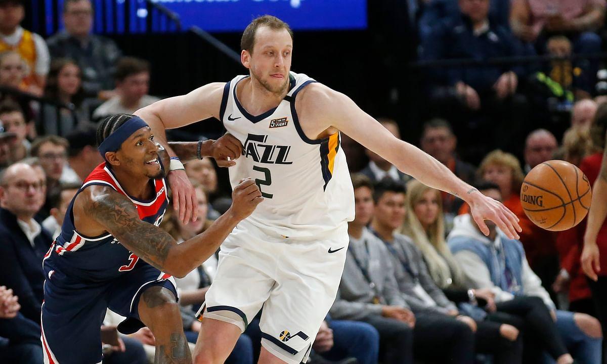Washington Wizards guard Bradley Beal, left, and Utah Jazz guard Joe Ingles (2) chase the ball in the first half during an NBA basketball game Friday, Feb. 28, 2020, in Salt Lake City. (AP Photo/Rick Bowmer)