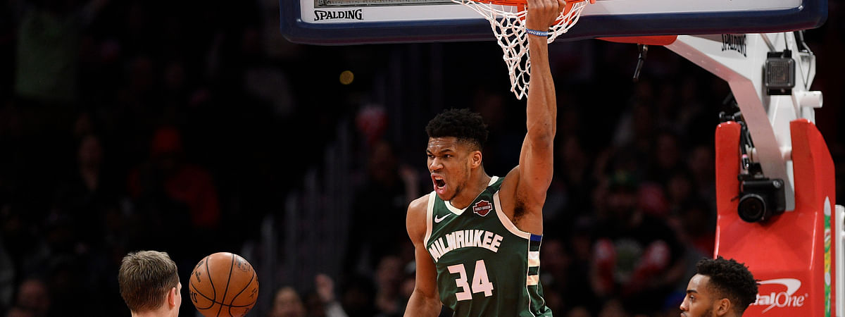 Milwaukee Bucks forward Giannis Antetokounmpo (34) hangs from the rim after his dunk during the second half of an NBA basketball game next to Washington Wizards forward Moritz Wagner (21) and forward Troy Brown Jr. (6) , Monday, Feb. 24, 2020, in Washington. (AP Photo/Nick Wass)