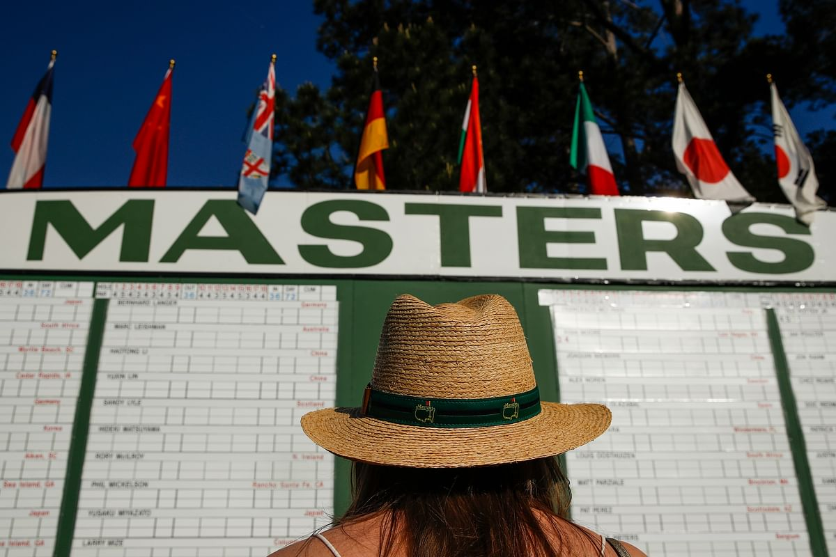 FILE - In this April 5, 2018, file photo, Anna Lee Lavarnway looks at the leaderboard during the first round at the Masters golf tournament in Augusta, Ga. Augusta National decided Friday, March 13, 2020, to postpone the Masters because of the spread of the coronavirus. Club chairman Fred Ridley says he hopes postponing the event puts Augusta National in the best position to host the Masters and its other two events at some later date. Ridley did not say when it would be held. (AP Photo/Charlie Riedel, File)
