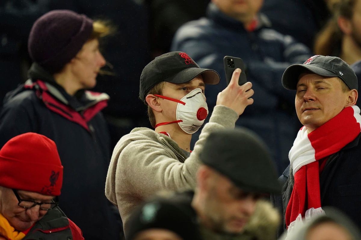 A fan wears a mask to helps protect himself from the new coronavirus attends a second leg, round of 16, Champions League soccer match between Liverpool and Atletico Madrid at Anfield stadium in Liverpool, England, Wednesday, March 11, 2020. (AP Photo/Jon Super)