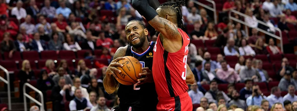 Los Angeles Clippers' Kawhi Leonard (2) drives toward the basket as Houston Rockets' Robert Covington defends during the first half of an NBA basketball game Thursday, March 5, 2020, in Houston.